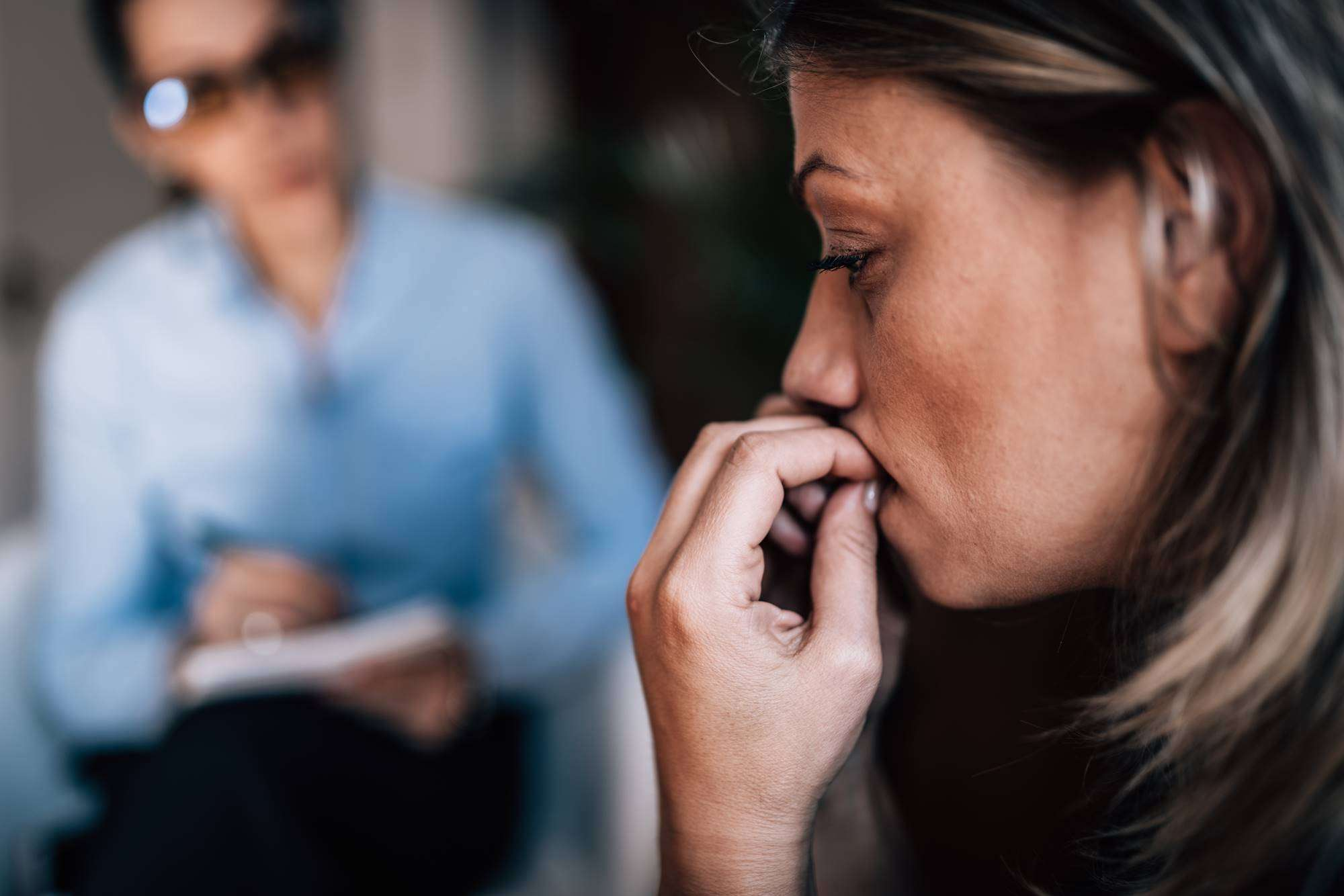 Woman with Anxiety Disorder, Biting Fingernails, Talking to Mental Health Professional