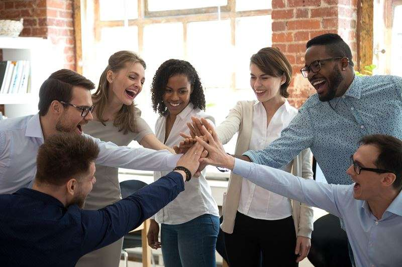 Happy diverse colleagues give high five together celebrate great teamwork